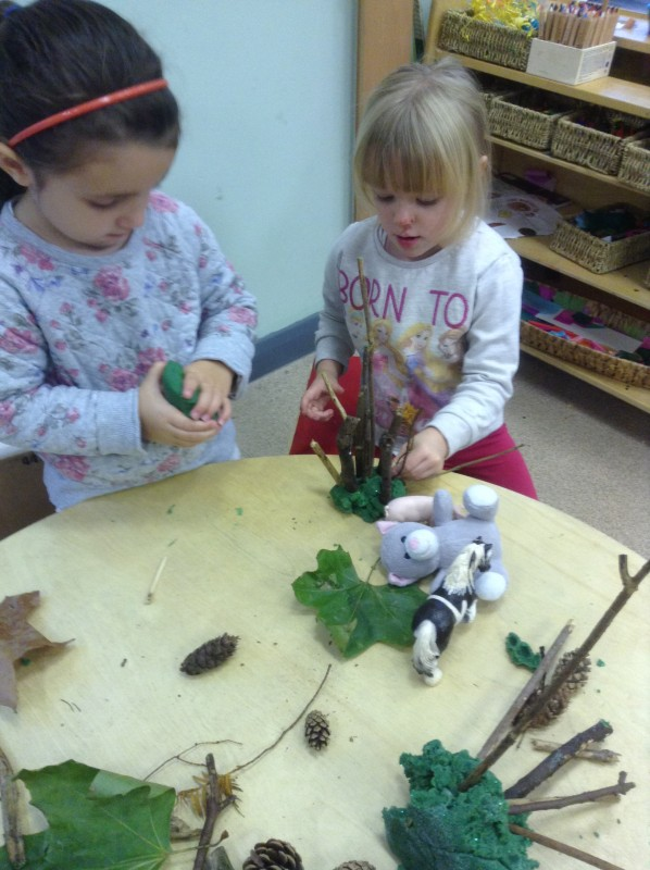 The girls are working together to make a forest using play dough and some natural materials.